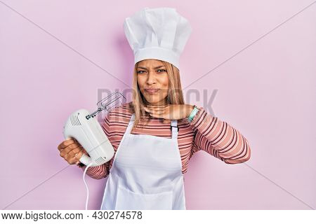 Beautiful hispanic woman holding pastry blender electric mixer cutting throat with hand as knife, threaten aggression with furious violence