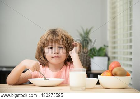 Portrait Of Cute Child Eating Soup Meal Or Breakfast Having Lunch By The Table At Home With Spoon. K