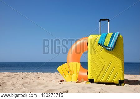 Suitcase And Beach Accessories On Seaside. Space For Text
