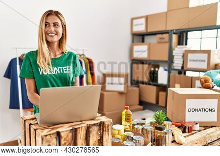 Young caucasian volunteer girl using laptop working at charity center.