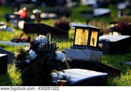 Grave Lantern With Yellow Glass Shining In The Back Light On A Gravestone In A Cemetery Against Blur