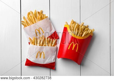 Mykolaiv, Ukraine - August 12, 2021: Small And Big Portions Of Mcdonald's French Fries On White Wood