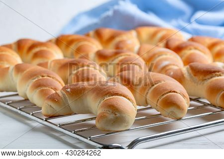 Freshly Baked Rolls, Rolled Into A Crescent, On A Baking Sheet Lined With Parchment. Concept Of Home