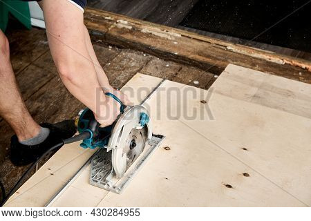 Sawing Plywood By Circular Saw. Home Repair. Hand Tool. Man Hold Equipment. Building Process. Woodwo