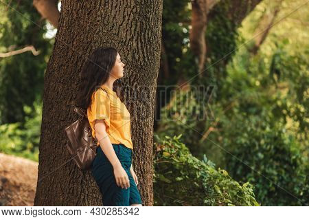 A Lonely Young Caucasian Woman Stands Leaning On The Trunk Of A Large Tree And Looks To The Right Si