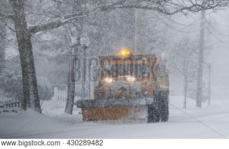 Babylon, New York, Usa - 1 February 2021: A Yellow Municipal Snowplow Truck Is Clearing A Road While
