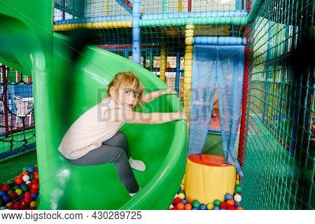 Active Little Girl Playing In Indoor Playground. Happy Joyful Preschool Child Climbing, Running, Jum