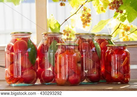 Preserves vegetables in glass on wood background, marinated fermented and pickled fermer food
