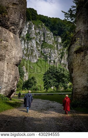 A Couple In Storm Coats Walking Through A Rock Gate.  A Picturesque Limestone Rock Formation Called