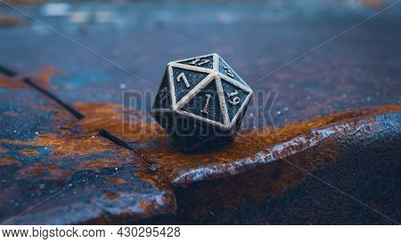 Close-up Image Of One  20-sided Metallic Role-playing Die On A Rusty Surface In Cool Light.