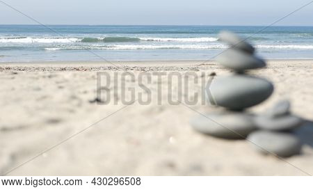 Rock Balancing On Ocean Beach, Stones Stacking By Sea Water Waves. Pyramid Of Pebbles On Sandy Shore