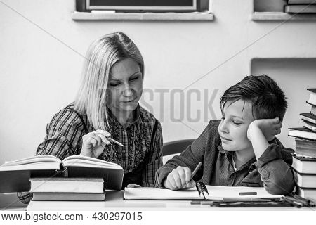 Student elementary school with the help of a tutor. Black and white photo.