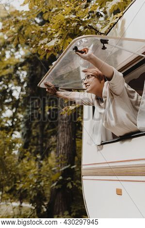 Young Woman Opening Camping Van Window In The Morning In Autumn Forest.