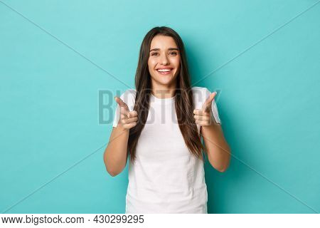 Cheerful Brunette Woman In White T-shirt, Congratulating You, Pointing Fingers At Camera, Smiling Pl