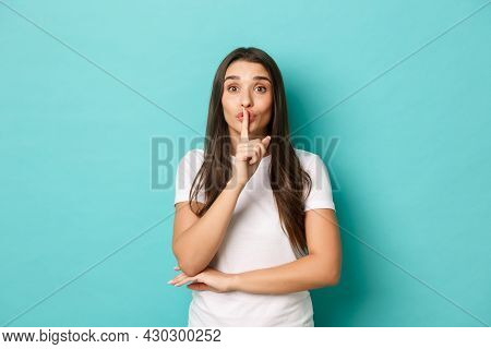 Portrait Of Cute Brunette Girl In White T-shirt, Hushing With Finger Over Lips, Telling A Secret, As