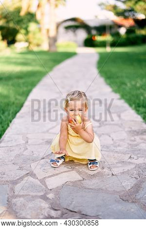 Little Girl Squatting On A Paved Path In The Park And Nibbling An Apple