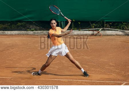 Beautiful Young Sportswoman, Professional Tennis Player With Racket Practicing On Clay Tennis Court
