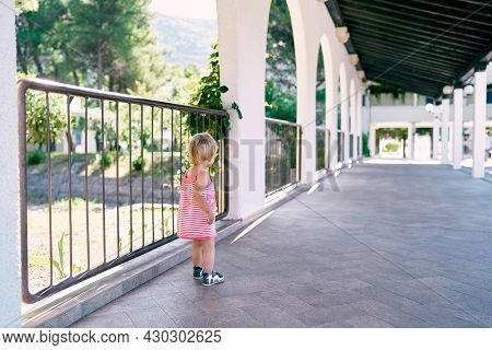 Little Girl Stands Near A Fence In A Long Pavilion In The Park. Back View