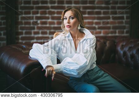 Glamorous middle-aged woman with enlarged full lips and evening makeup sitting on a leather sofa. Luxury lifestyle. High fashion shot.