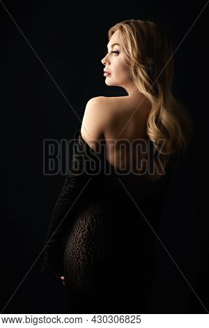 Portrait of a wealthy mature woman with evening makeup and hairstyle posing in black dress on a black background. Luxury lifestyle. Cosmetology, plastic surgery, rejuvenation.