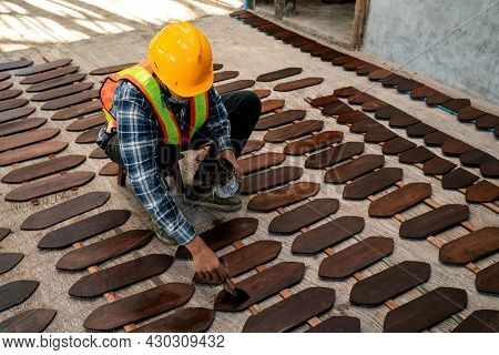 Worker Painting Or Varnish On Wooden Board On Construction Site.