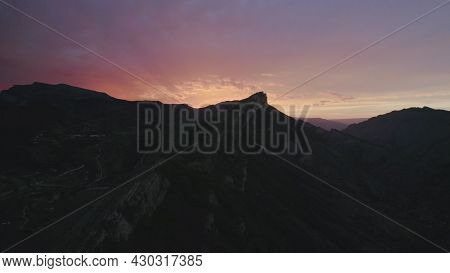 Top View Of Mountain On Background Of Purple Sunset Sky. Action. Dark Silhouettes Of Mountains On Ba