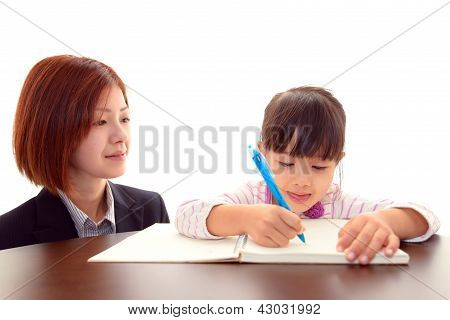 Little Asian girl studying with teacher