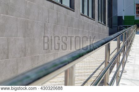 A Ramp With Stainless Steel Handrails For Wheelchairs, Bicycles And Strollers With Children In Front