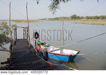 Peaceful Landscape With A Blue Boat Next To A Wooden Pier. Rice Fields In The Distance. Comporta, Po