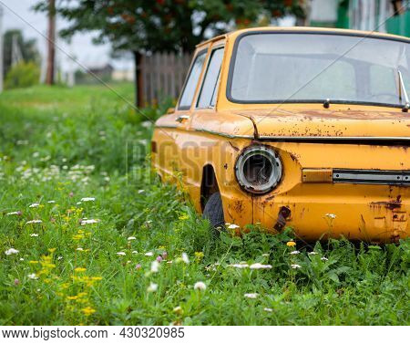 Old Yellow Wrecked Car In Vintage Style. Abandoned Rusty Yellow Car. Close-up Of The Headlights Of T
