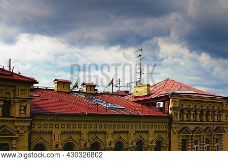 Satellite Dishes And Tv Antennas On The House Roof With A Cloudy Sky. Red Tile Roof With Different T