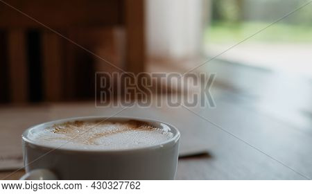 Cappuccino Or Coffee Latte On A Wooden Table. Close-up, Selective Focus, Sunlight From The Window. C