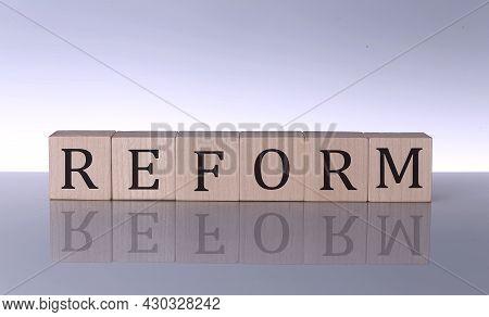 Reform Concept, Wooden Word Block On Grey Background