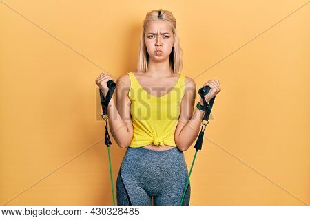 Beautiful blonde woman training arm resistance with elastic arm bands puffing cheeks with funny face. mouth inflated with air, catching air.