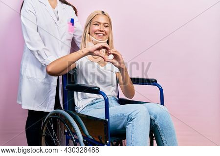 Beautiful blonde woman sitting on wheelchair with collar neck smiling in love doing heart symbol shape with hands. romantic concept.