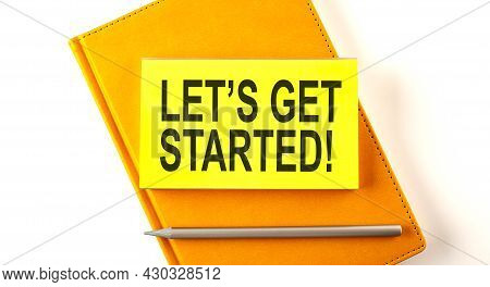 Text Let's Get Started On The Sticker On Yellow Notebook