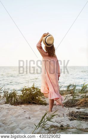 A Beautiful Young Girl On The Beach In A Pink Dress And A Straw Hat In Her Hands. Summer Content, Su