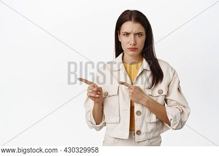 Sad And Gloomy Girl Furrow Eyebrows, Pointing Left At Sale With Regret Or Jealousy, Unfair Situation
