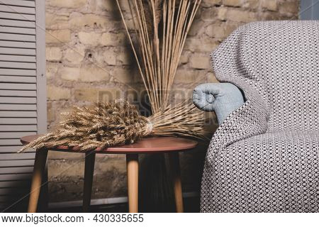 Empty Comfortable Soft Armchair Covered With Gray Bedspread And Coffee Table. Dried Sheaf Of Wheat O