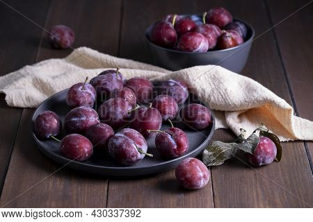 Close-up Of Fresh Ripe Purple Plums In A Dish On A Table From Natural Dark Wooden Boards. Rustic Har