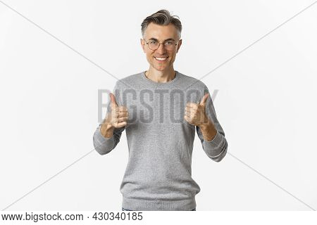 Image Of Confident And Satisfied Middle-aged Man, Smiling Pleased, Showing Thumbs-up, Wearing Grey S