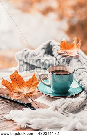 Autumn Morning Coffee. A Cup Of Coffee On A Wooden Table And A Warm Sweater On A Background Of Autum