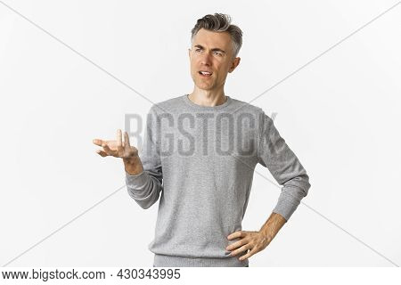 Image Of Confused Middle-aged Man Cant Understand Something, Raising Hand And Looking Puzzled Left,