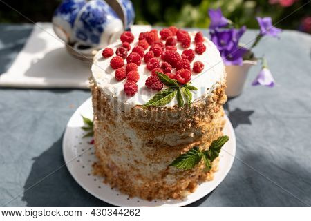 Raspberry Homemade Cake On A Table In The Garden On A Sunny Summer Morning, A Small Bouquet Of Garde