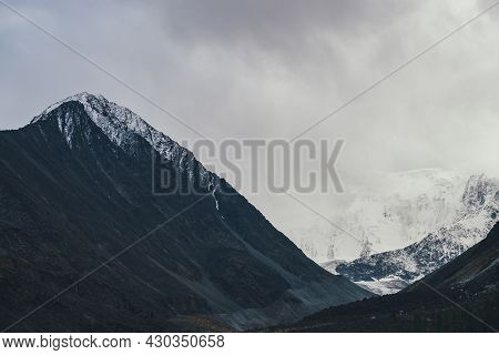 Dark Atmospheric Landscape With High Black Mountain Top And Snow-covered Mountain Wall In Low Clouds