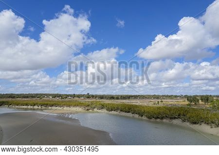 Aerial Landscape Of Mud Flats At Low Tide With A Small Township In The Distance Under A Cloudy Blue