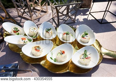 Snacks In White Bowls On A Golden Plate In The Form Of The Tree Leaf