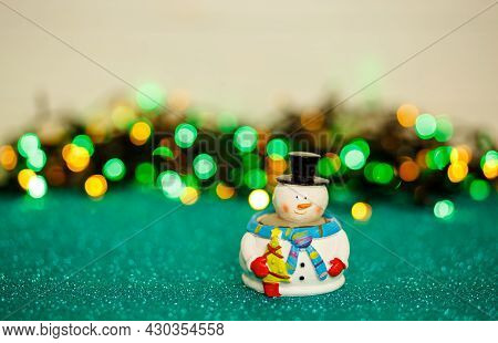 Snowman On Abstract Background. Christmas Snowman On The Table Against A Bokeh Lights Back. Snowman