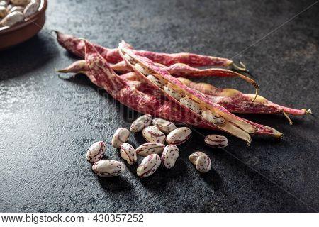 Cranberry beans. Borlotti beans. Beans pods on black table.