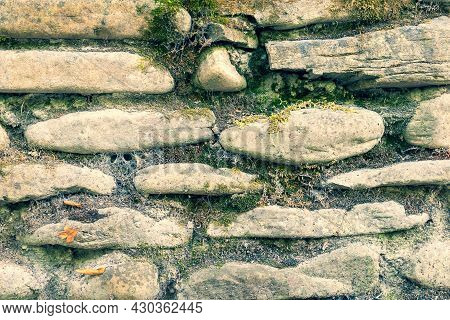 Close Up And Soft Focus Of An Old Wall With A Masonry Of Weathered Stones Overgrown With Moss In Rur